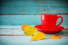 与干燥叶子和热的咖啡的秋天背景 免版税库存图片