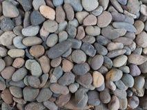 与干燥圆的小卵石石头的背景 免版税库存图片