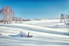 与干草卷的明亮的美好的冬天风景在雪的 免版税库存图片