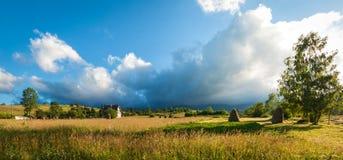 与干草堆的农村风景在一个夏天晴天 与暴风云的农村山风景 图库摄影