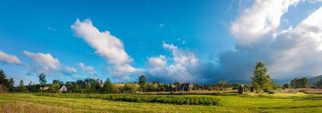 与干草堆的农村风景在一个夏天晴天 与暴风云的农村山风景 免版税图库摄影