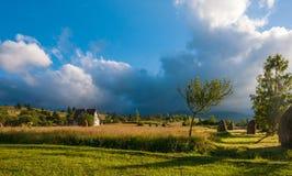 与干草堆的农村风景在一个夏天晴天 与暴风云的农村山风景 库存照片