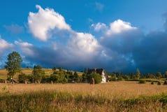 与干草堆的农村风景在一个夏天晴天 与暴风云的农村山风景 免版税库存照片