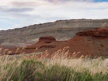与干草的红色岩层在前景 免版税库存照片