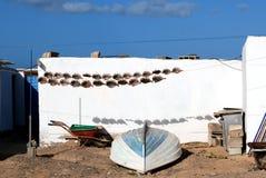 与干鱼和一条小船的五颜六色的场面在一个远程位置的前面ATraditional渔小屋加那利群岛的 免版税库存照片