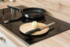 与平底锅和切开板材的现代陶瓷烹调表面 库存图片