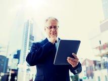 与平板电脑的资深商人在城市街道上 图库摄影