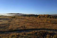 与平衡在日落的天空一个美好的梯度的农村风景反对绿色领域背景  库存照片