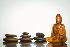 与平衡的小卵石的木菩萨雕象 库存图片