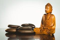 与平衡的小卵石的木菩萨雕象 图库摄影