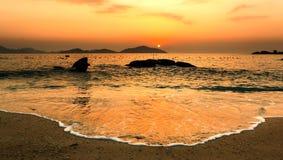 与平静的海滩、岩石、海岛和波浪的自然海景在华美的橙色日出 免版税图库摄影