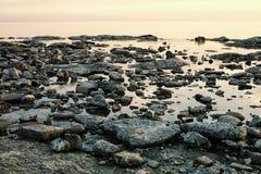 与平面镜象海和岩石的海景在日落的岸 免版税库存图片