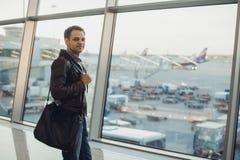 与年轻人的旅行概念机场内部的有城市视图和平面飞行 库存照片