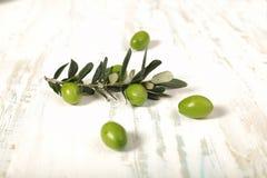 与年轻橄榄色的枝杈的被收获的新鲜的橄榄在木backgroun 库存照片