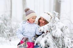 与年轻母亲和儿童女儿的愉快的家庭在一个冬天走户外 免版税库存照片