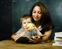 与年轻真正的老师,教室studyin的小的逗人喜爱的男孩学生 免版税库存照片
