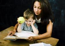 与年轻真正的老师,教室studyin的小的逗人喜爱的男孩学生 免版税库存图片
