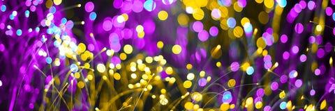 与幻想bokeh纹理紫色氖和金黄颜色的抽象背景 时兴的圣诞节背景 库存图片