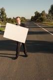 与广告牌的商人在路 免版税库存图片
