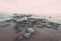 与广角透视的岩石海海滩 葡萄酒 葡萄酒 免版税库存照片