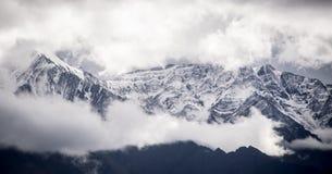 与庄严云彩的令人惊讶的多雪的穿的峰顶 免版税图库摄影