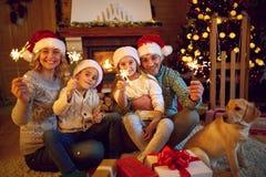 与庆祝圣诞节的闪烁发光物家庭的圣诞快乐 库存图片