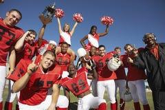 与庆祝在领域的啦啦队员和教练的橄榄球队成功 免版税库存图片