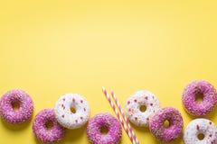 与庆祝项目的桃红色和白色油炸圈饼在黄色背景 免版税库存照片