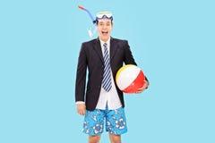 与废气管和海滩球的激动的商人 免版税库存图片