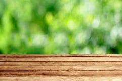 与庭院夏天bokeh室外题材backgrou的空的木桌 免版税库存照片