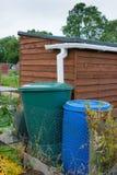 水与庭院棚子的存贮桶 免版税库存图片