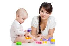 与建筑集合玩具一起的女婴和母亲作用 库存照片