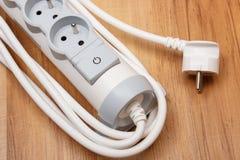 与开关的电能小条开-关在木地板上 免版税图库摄影
