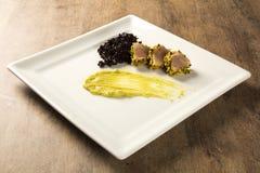 与开心果外壳、黑米和鲕梨纯汁浓汤的金枪鱼 库存照片