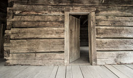 与开放前门的历史原木小屋 免版税库存照片