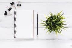 与开放嘲笑的白色办公桌木桌背景笔记本和笔和植物 库存图片