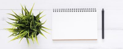 与开放嘲笑的白色办公桌木桌背景笔记本和笔和植物 免版税库存照片