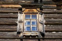 与开放快门的老窗口玻璃与在乡下木屋的木墙壁的背景的蓝天 免版税库存照片