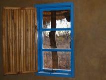 与开放板条板条的明亮的蓝色窗口wooeden快门和看法 图库摄影