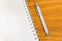 与开放白色笔记本的白色小点笔有在木表上的线的 图库摄影