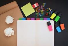 与开放笔记本、工艺、五颜六色的轮廓色_、夹子和别针的创造性的工作区在黑书桌上 库存图片