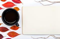 与开放笔记本和咖啡的五颜六色的秋叶 免版税库存照片