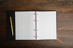 与开放笔记本和笔的企业概念在木backgrou 库存图片