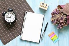 与开放笔记本纸、立方体日历和时钟的书桌桌 免版税库存图片