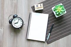 与开放笔记本纸、立方体日历和时钟的书桌桌 免版税库存照片