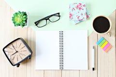 与开放笔记本纸、辅助部件和咖啡杯的办公桌桌 免版税图库摄影