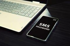 与开放膝上型计算机和黑被筛选的智能手机的表有在它的显示的白色文字SMS密码的 概念  库存图片