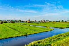 与开放领域、运河和荷兰风车的典型的荷兰风景 免版税库存图片