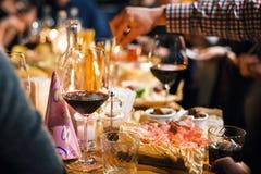 与开胃菜和酒板材的餐馆或酒吧桌  人们谈话在背景 被定调子的图片 免版税库存图片