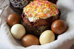 与开胃,美妙地装饰的复活节蛋糕的复活节构成,洗染了在一个篮子的鸡蛋在亚麻制织品,特写镜头,侧视图 免版税库存照片